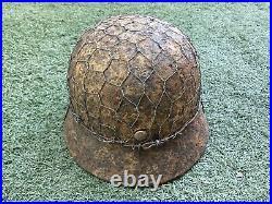 WW2 German combat helmet M35 with an original metal camouflage mesh. Size 65